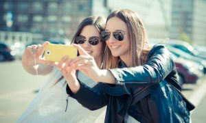 2 girls taking selfie on phone