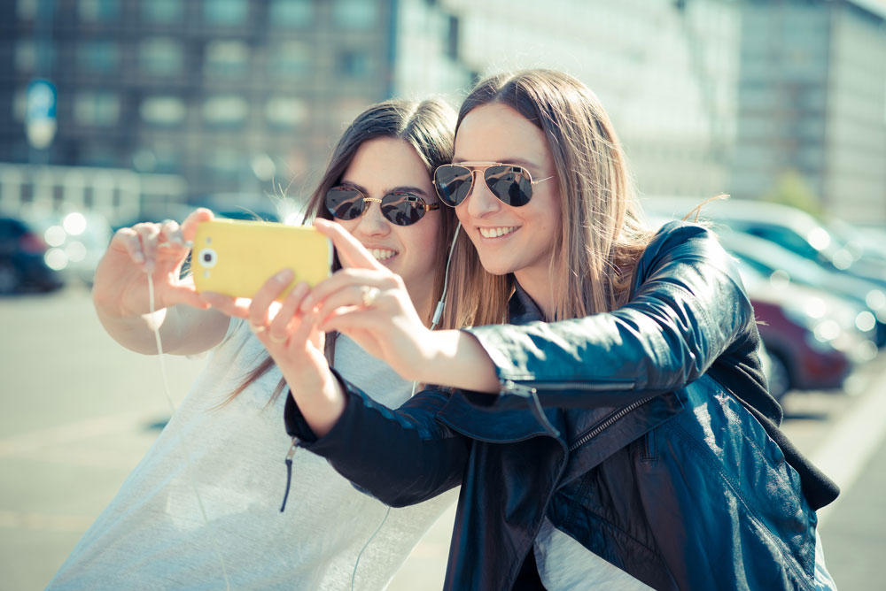 2 girls taking selfie on phone