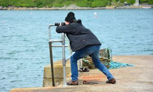 Photographer at harbour searching for the perfect image