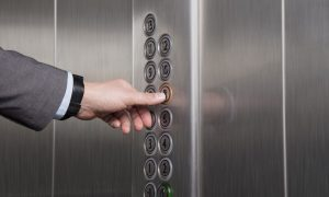 male hand pressing button on elevator