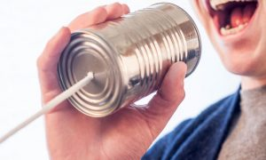 man speaking on tin can phone