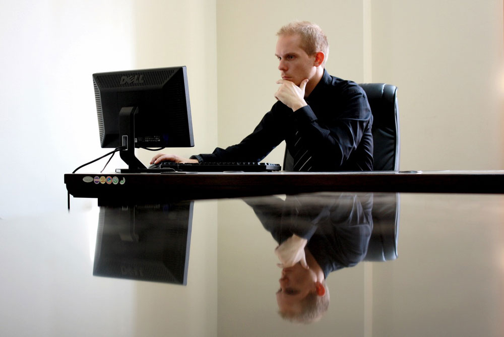 Business man reading proposal on computer screen