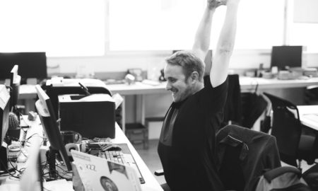 presentation designer stretching at desk