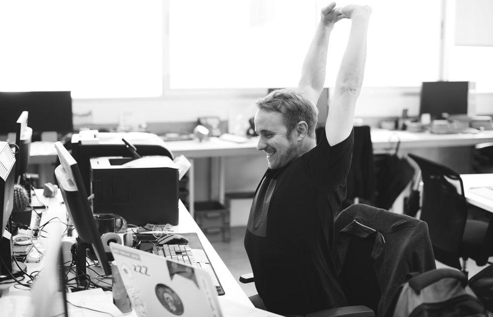 presentation designer stretching at desk