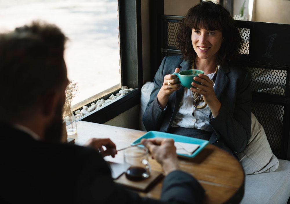 2 business people having conversation over coffee