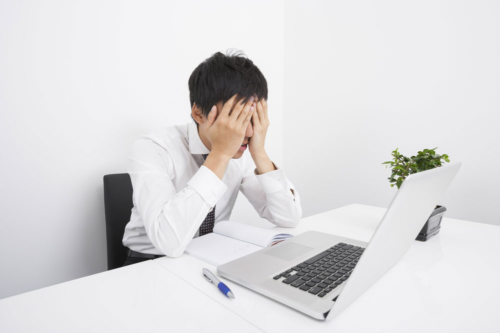 frustrated powerpoint user with head in hands looking at laptop