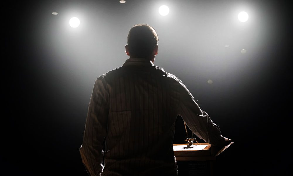 rear view of male professional speaker on stage under the spotlight