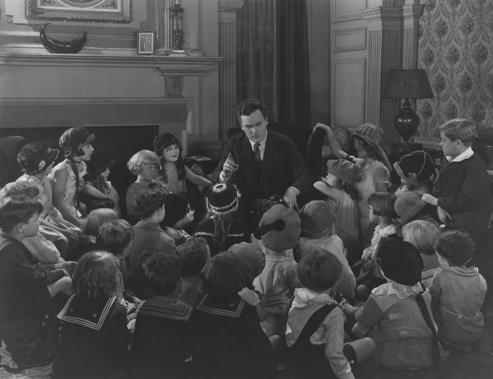 Storyteller with large group of children