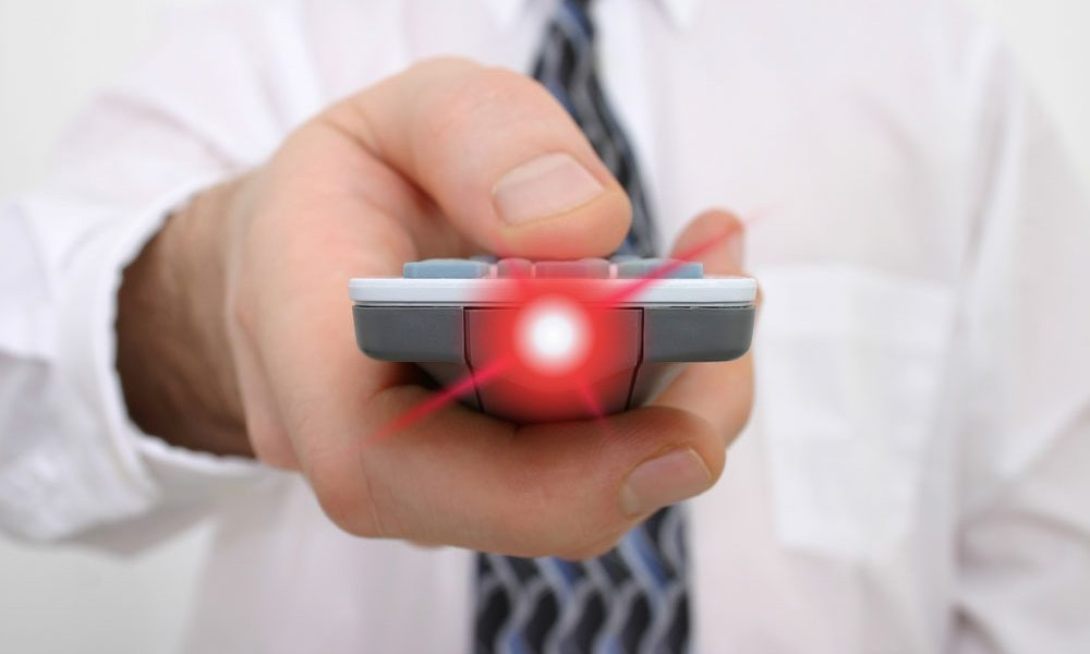 presenter in white shirt point presentation remote control with red laser light