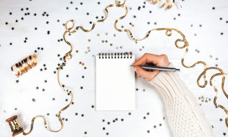 Ladies hand writing new year resolutions on pad surrounded by tinsel and glitter stars