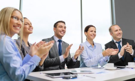 Smiling business people sat around table clapping successful impromptu speech