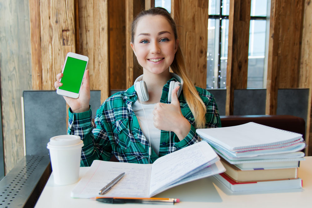 young student with large pile of books doing homework while listening to podcasts
