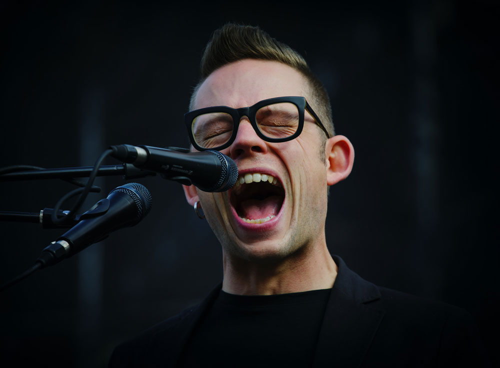 man performing vocal exercise shouting into microphone