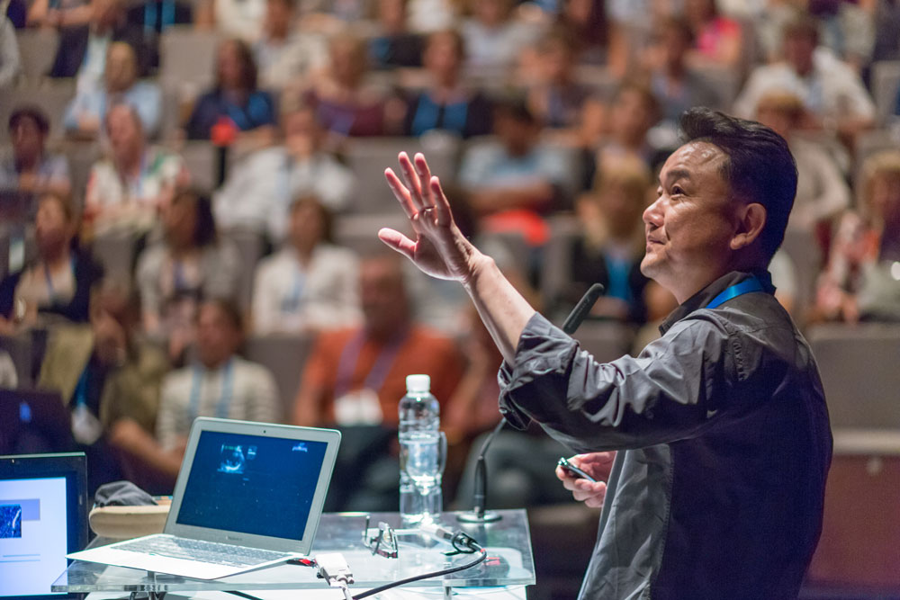 male presenter addressing large audience at scientific conference