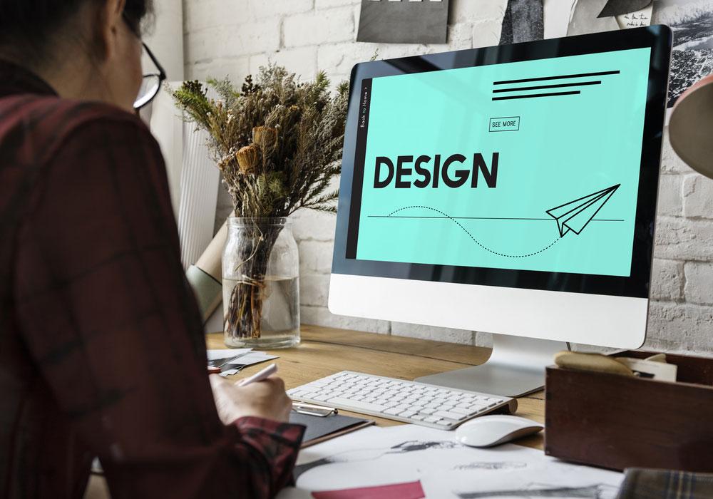 presentation designer sat at desk looking at presentation on computer screen