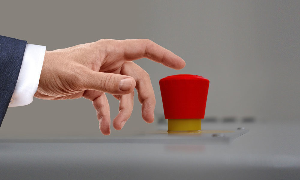 Hand reaching out to press red trigger